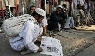 Ein Afghane liest eine Zeitung mit dem Bild von Hamid Karzai. (Foto)