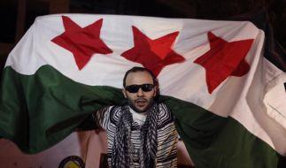 Ein Demonstrant hält die syrische Revolutionsflagge hoch. (Foto)