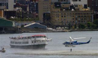 Ein Hubschrauber setzt einen Rettungstaucher im Hudson River ab. (Foto)