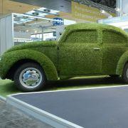 Ein mit Kunstrasen überzogener Volkswagen Käfer neben einer Ladesäule für Elektroautos auf der Hannover Messe - ein Modell für die Zukunft?