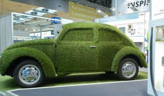 Ein mit Kunstrasen überzogener Volkswagen Käfer neben einer Ladesäule für Elektroautos auf der Hannover Messe - ein Modell für die Zukunft? (Foto)
