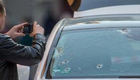 Ein Mitarbeiter der Spurensicherung fotografiert am 05. Mai 2016 in Frankfurt am Main (Hessen) die Einschusslöcher in der Windschutzseite des weißen Mercedes-Geländewagens. (Foto)