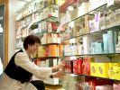 Ein Mitarbeiterin räumt in einer Douglas-Filiale in Köln Parfüm in ein Regal. (Foto)