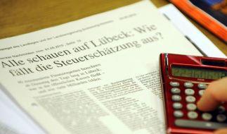 Ein Mitglied des Arbeitskreises Steuerschätzung tippt im Rathaus von Lübeck auf den Tasten seines Ta (Foto)