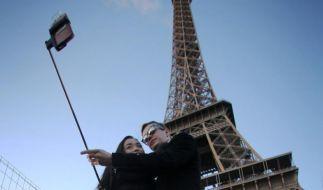 Ein Paar macht unter dem Eiffelturm ein paar Selfies. Damit könnte jedoch bald Schluss sein. (Foto)