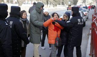 Ein chinesischer Polizist versucht, eine Protestantin vor dem Gerichtsgebäude vom Gespräch mit Journ (Foto)