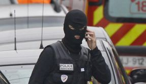 Ein Polizist telefoniert vor dem Wohnhaus, in dem sich Mohammed Merah verschanzt hält. (Foto)