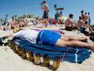 Ein schlafender Tourist liegt neben leeren Bierflaschen am Strand von Arenal. (Foto)