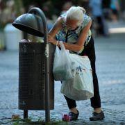 Eine ältere Frau sucht nach Pfandflaschen - ein leider gängiges Bild in Deutschland.