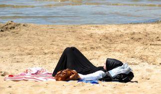 Eine junge Frau entspannt am Wannsee. Weil sie ein Kopftuch trägt, wird sie gleich als Muslima erkannt und hervorgehoben. Muss das sein? (Foto)