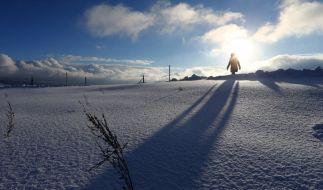 Eine Spaziergängerin läuft im Sonnenschein durch die tief verschneite Landschaft bei Scheidegg (Bayern). (Foto)