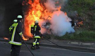 Feuerwehrleute bei Löscharbeiten eines Fahrzeugs auf einer Landstraße bei Petersberg in Hessen. Bei dem Unfall waren drei Autoinsassen verbrannt. (Foto)
