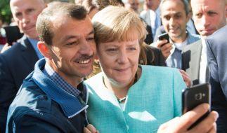 """Foto mit """"Mutti"""": Als Bundeskanzlerin Angela Merkel ein Flüchtlingsheim besucht, wollen einige Bewohner Bilder mit ihr schießen. Die Flüchtlingskrise beherrschte die Medienlandschaft wie kein anderes Thema 2015. (Foto)"""