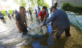 Helfer schichten Sandsäcke in einer überfluteten Straße in Magdeburg zu Dämmen auf. (Foto)