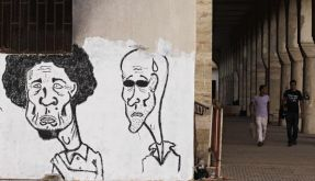In this Monday, July 4, 2011 photo, caricatures of Libyan dictator Moammar Gadhafi, left, and his so (Foto)
