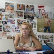 Inna Schewtschenko sitzt in der Femen-Zentrale in Kiew vor einer Wand voller Zeitungsartikel über ihre Aktionen.