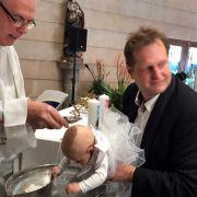 Jens Büchner mit seinen Zwillingen bei der Kindertaufe. (Foto)