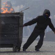 Ein maskierter Randalierer zieht einen brennenden Müllcontainer durch Straßen im Osten Londons.