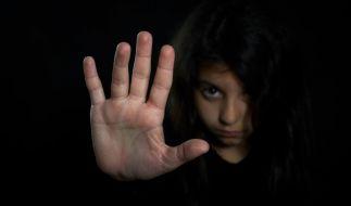 Mädchen, das mit erhobener Hand Missbrauch und Vergewaltigung abwehrt. (Foto)