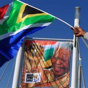 Der Vater der Nation hat Geburtstag: Während der Fußball-WM schwenkt ein Fan die südafrikanische Flagge vor einem Porträt Mandels.