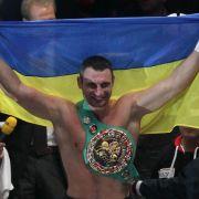 Mit ukrainischer Fahne und Weltmeistergürtel feiert Vitali Klitschko seine Titelverteidigung.