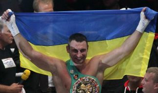 Mit ukrainischer Fahne und Weltmeistergürtel feiert Vitali Klitschko seine Titelverteidigung. (Foto)