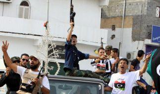 Mit Freudenschreien und Gewehrsalven feiern die Menschen den Tod des Ex-Diktators.  (Foto)