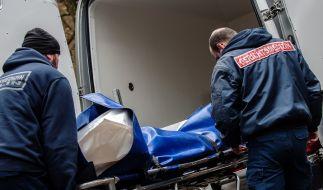 Mitarbeiter der Gerichtsmedizin bringen die Leiche zu ihrem Fahrzeug. (Foto)