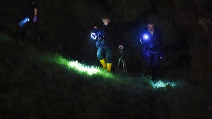 Nach dem grausigen Fund suchen Polizisten den Uferbereich mit Taschenlampen. (Foto)