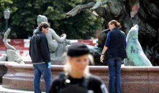 Polizeibeamte untersuchen den Tatort am Neptunbrunnen vor dem Roten Rathaus in Berlin. (Foto)