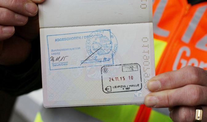 Polizist zeigt den Pass eines serbischen Asylbewerbers, der abgeschoben wird. (Foto)