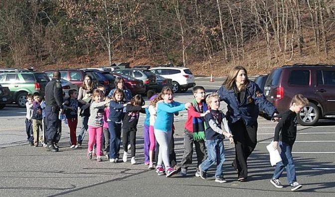 Polizisten evakuieren Kinder aus der Grundschule. (Foto)