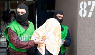 Polizisten führen bei einer Razzia gegen Islamisten am 04.02.2016 in Berlin einen mit einem Tuch verdeckten Verdächtigen ab. (Foto)