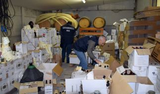 Polizisten durchsuchen in der Nähe von Florenz (Italien) ein Lager, in dem gefälschter Rotwein entdeckt wurde. (Foto)