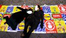 Aktivisten liegen in Berlin während einer Aktion für die Einhaltung der Menschenrechte und des Arbeitsrechts auf Plastiktüten verschiedener Supermarktketten. Die Aktivisten wenden sich mit der Aktion gegen die Preispolitik der Discounter und die damit verbundenen Auswirkungen auf deren Arbeitnehmer. Foto: ddp