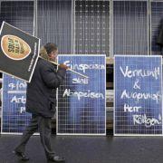 Ein Beschäftigter einer Solarfirma geht während einer Protestveranstaltung gegen die geplanten Subventionskürzungen für die Branche an bemalten Solartafeln im Solar Valley in Thalheim vorbei (Archivbild).