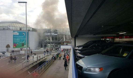 Rauch steigt über dem Terminal des Brüsseler Flughafens auf. Scheiben sind zerstört, Menschen fliehen. (Foto)