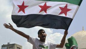 «Rettet die syrischen Kinder» stht auf dem T-Shirt des Regimegegners. Er schwenkt die Flagge der Rebellen. (Foto)