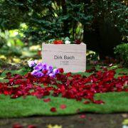 Rote Rosenblätter schmücken die letzte Ruhestätte des Schauspielers Dirk Bach.