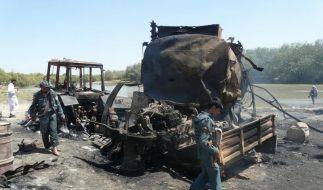 Sicherheitsbeauftragte inspizieren die ausgebrannten Tanklastzüge in Kundus nach dem Luftangriff. (Foto)