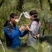 So geht es richtig: Der britische Abenteurer Bear Grylls zeigt drei jungen Pfadfindern, wie sie die Sauerstoffmasken benutzen müssen.