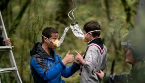 So geht es richtig: Der britische Abenteurer Bear Grylls zeigt drei jungen Pfadfindern, wie sie die Sauerstoffmasken benutzen müssen. (Foto)