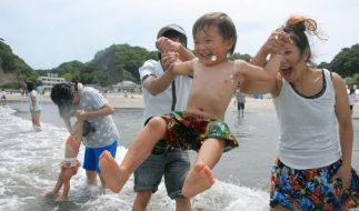 Spaß am Strand: Eltern und ihr Sohn baden im Pazifik bei Iwaki, dem ersten wiedereröfneten Strand nach dem Super-Gau. (Foto)
