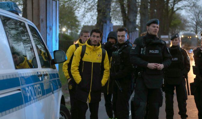 Spieler von Borussia Dortmund, darunter Sven Bender und Nuri Sahin, werden von Polizisten zum Hotel gebracht.