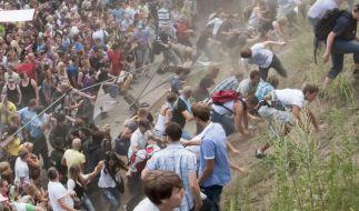Teilnehmer der Loveparade durchbrechen nach einer Massenpanik mit Toten Absperrgitter. Jetzt ermitte (Foto)