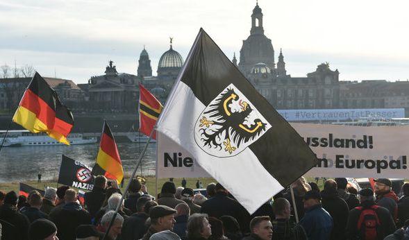 Teilnehmer einer Pegida-Demonstration in Dresden mit Deutschlandflaggen und einer Ostpreußen Fahne. (Foto)