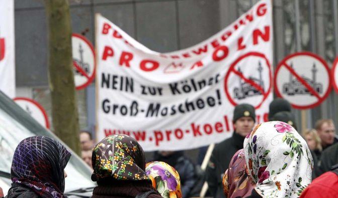 Türkische Frauen beobachten eine Demonstration gegen eine Moschee in Köln. (Foto)