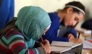 Türkisches Mädchen mit Kopftuch schreibt im Schulunterricht etwas auf. (Foto)