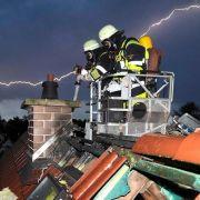 Unwetter und kein Ende: Feuerwehrleute löschen während eines Gewitters einen Dachstuhlbrand in München.