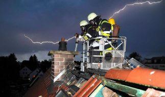 Unwetter und kein Ende: Feuerwehrleute löschen während eines Gewitters einen Dachstuhlbrand in München. (Foto)